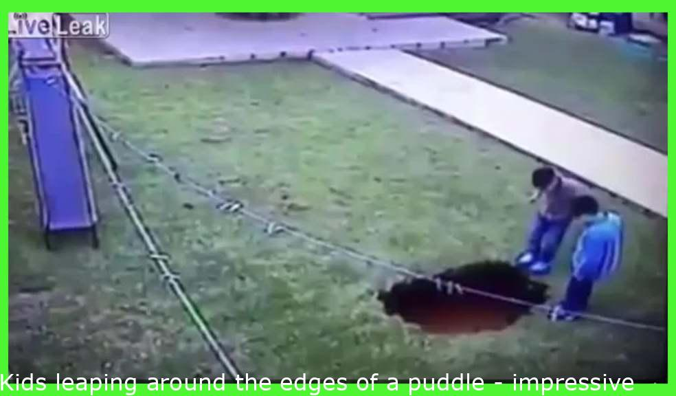 Kids jumping around the edges of a puddle